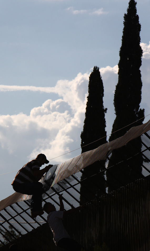 Men scale the fence into Nogales, Arizona from the Mexico side